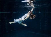 Mädchen im weißen Kleid unter Wasser