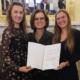 stolze Schülerinnen mit Lehrerin und Auszeichnungsurkunde