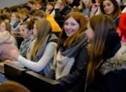 Schülerin im Hörsaal lächelt in die Kamera